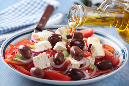 Pouring olive oil into Greek salad photo
