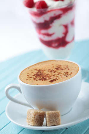 Cup of black coffee and raspberry parfait photo