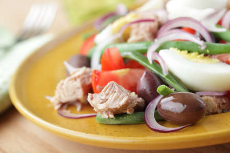 Nicoise salad with tuna and vegetables closeup. Shallow DOF photo