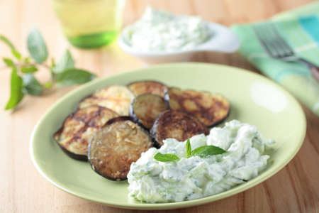 Tzatziki and roasted slices of eggplant on a plate photo
