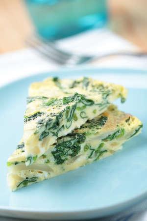 Twee plakjes frittata met spinazie en ui op een blauwe plaat