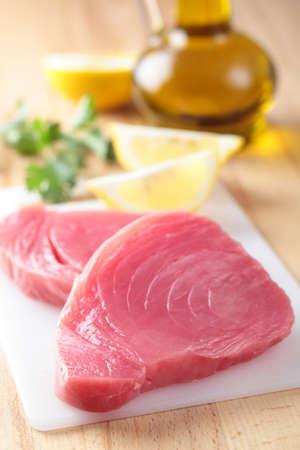 �tuna: Filetes de At�n crudo sobre una placa de corte Foto de archivo