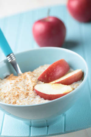 childrens food: Oatmeal porridge with cinnamon and apple in a bowl