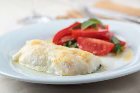 cod fish: Baked cod fillet with tomato and basil salad