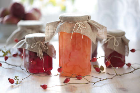 Autumn canning: jars with jam on a wooden table photo