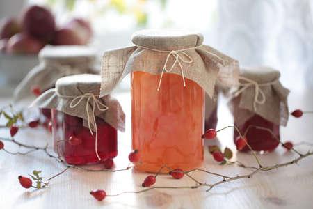 Herfst inblikken: potten met jam op een houten tafel Stockfoto