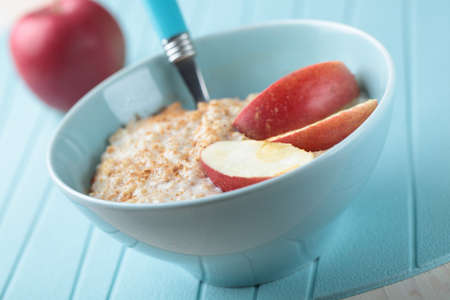 Oatmeal porridge with cinnamon and apple in a bowl photo