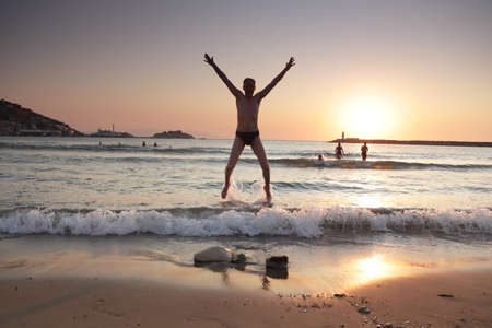 aegean sea: Jumping man against sunset over a beach on Aegean sea