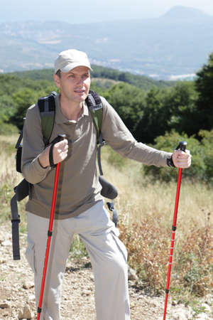 Hiker with trekking poles and backpack on mountain trail photo