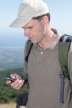 Hiker with mobile phone and backpack in mountains Stock Photo - 11003967