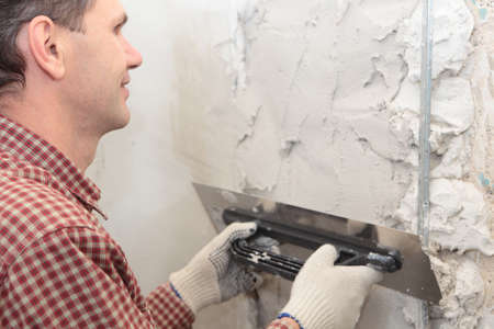 skimming: Worker plastering a wall using trowel