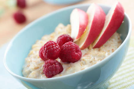 Oatmeal porridge with raspberry and apple in a bowl photo