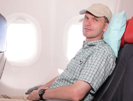 cushion: Passenger in airplane seat with pillow Stock Photo