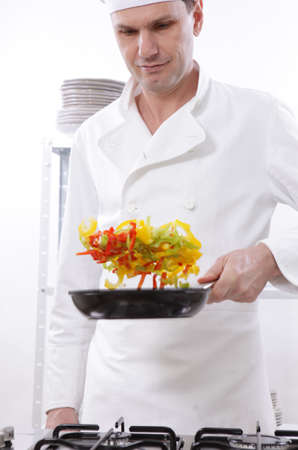 Chef roasting vegetables on a kitchen photo