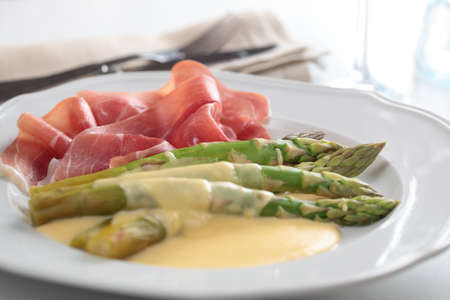 Prosciutto with steamed asparagus under cheese sauce photo
