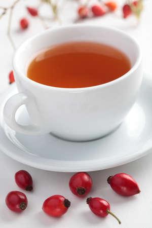 Rose hip tea in white cup closeup photo