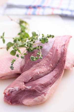 Raw goose breast with marjoram on a cutting board