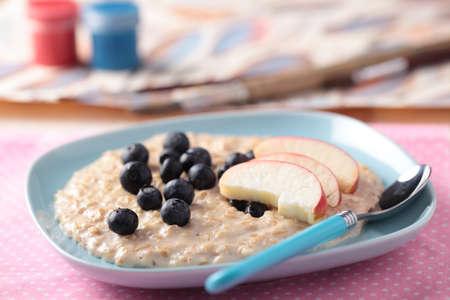 oatmeal: Ni�os un desayuno con copos de avena y frutas Foto de archivo