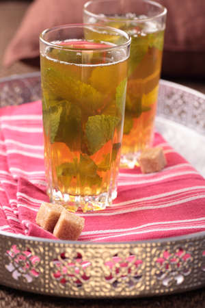 Moroccan mint tea and brown sugar on a tray photo