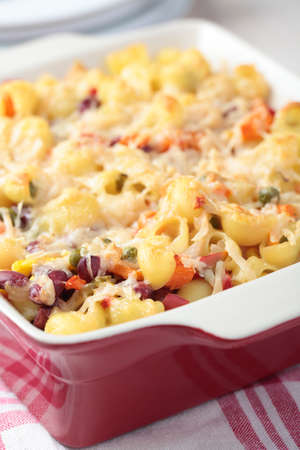 Macaroni cheese with vegetables and beans in a baking dish photo