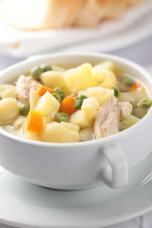 Chicken noodle soup in a white bowl closeup. Shallow DOF photo