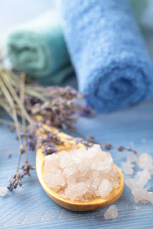Bath salt in a wooden spoon and lavender against rolled towels photo