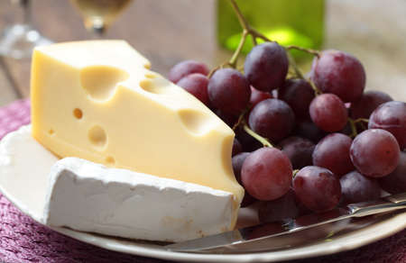 Grapes and two varieties of cheese on a plate photo
