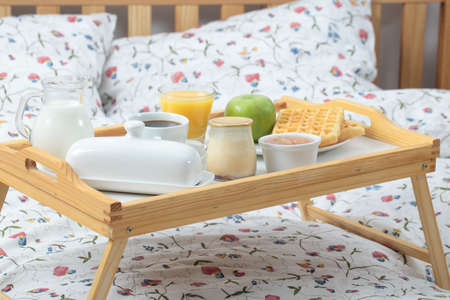 Tray with breakfast on a bed photo