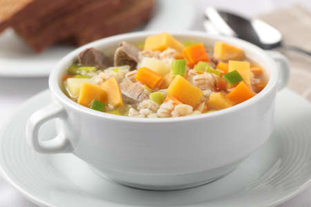 broth: Scotch broth with lamb meat in white bowl closeup