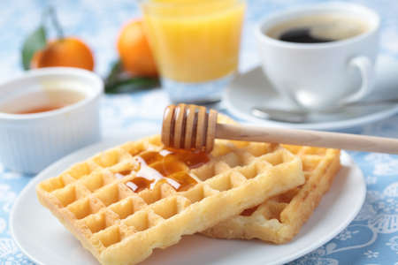 Breakfast with Belgian waffles, honey, orange juice and coffee photo