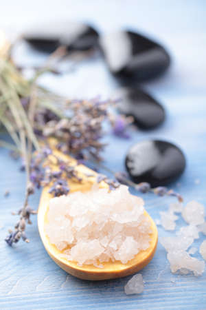 Bath salt in a wooden spoon and lavender against black pebbles photo