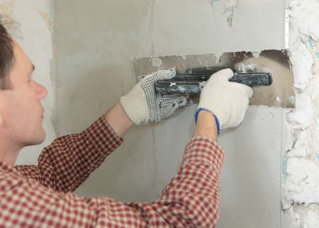 plastering: Worker plastering a wall using trowel