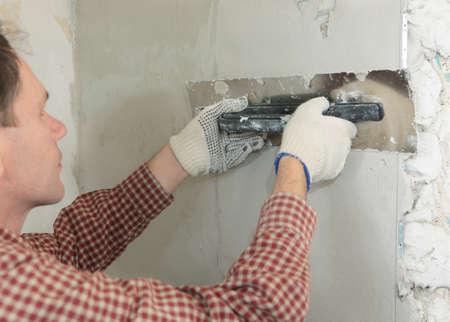 Worker plastering a wall using trowel