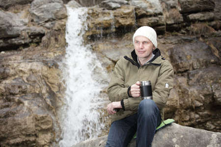 Tourist making a break with a mug of hot drink against waterfall photo