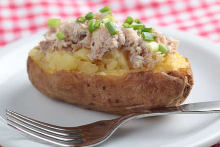 Baked potato with tuna salad and green onion on white plate photo