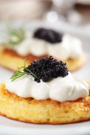 Blinis with black caviar and sour cream photo