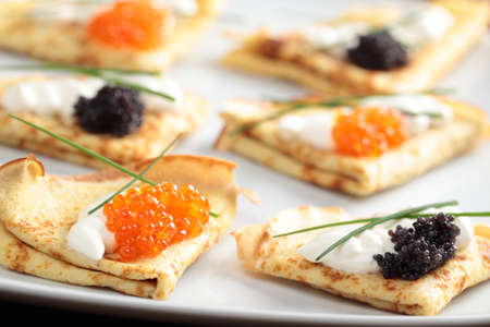 Blinis with red and black caviar on a plate