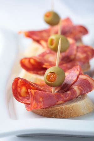 Canapes with chorizo and green olives stuffed with paprika photo