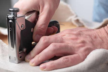 grapadora: El hombre tapizar una silla taburete redondo Foto de archivo