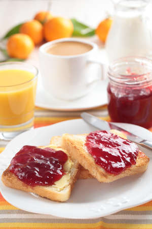Breakfast with toasts, butter, jam, orange juice, coffee, milk, and mandarin oranges photo