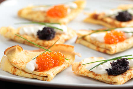pancake week: Crepes with red and black caviar on a plate Stock Photo