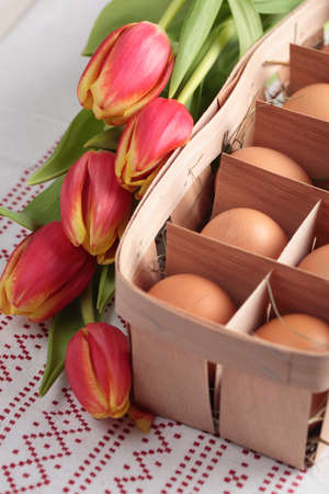 Eggs in a basket and a bunch of tulips photo