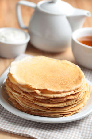 pancake week: Stack of crepes, tea, and sour cream on a table