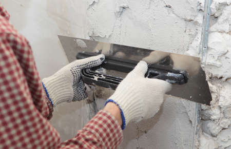Worker plastering a wall using trowel photo