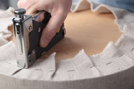 Man stofferen een ronde kruk stoel Stockfoto