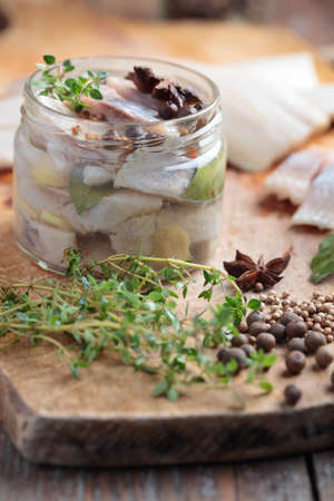 Homemade marinated herring in a jar with spices photo