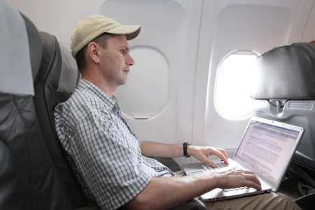 Passenger working with laptop in an airplane photo