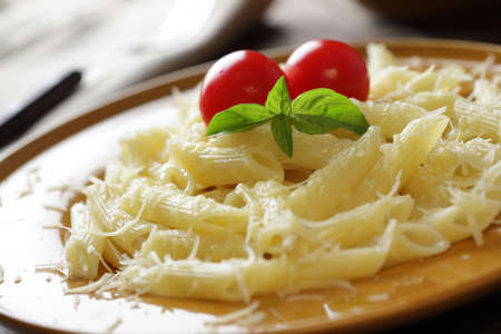 Macaroni with Parmesan cheese, tomatoes, and basil leaf photo