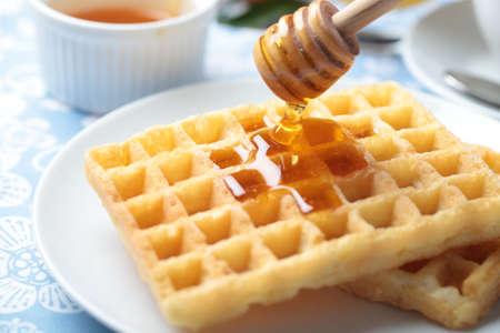 wafles: Verter la miel en waffles belgas con cucharón de miel Foto de archivo