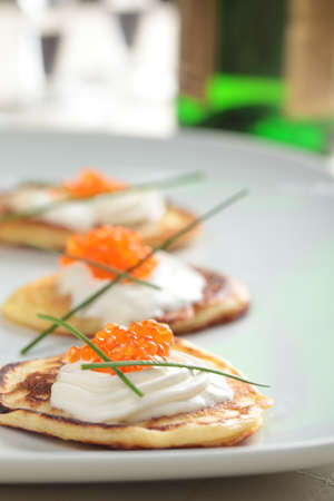 Blinis with red caviar on a plate photo